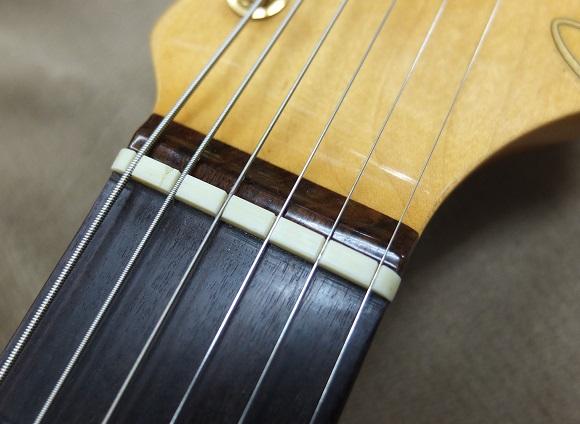 ナット。1弦の開放に少しビリツキがあります。おそらく、前オーナー様が太い弦を張っていたことで溝が広めになっていることが原因かと思います。あと5弦溝の脇に亀裂がありますが、破断には至っておらず、機能上は問題ありませんが、使う弦やお好みに応じてナットを交換をしても良いかと思います。
