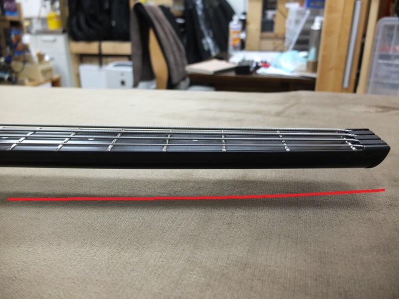 ネックのローポジション側はトラスロッドでは調整できない赤線のような起き上がりがあります。(わかりやすくするため赤線はかなり大袈裟にしています)。