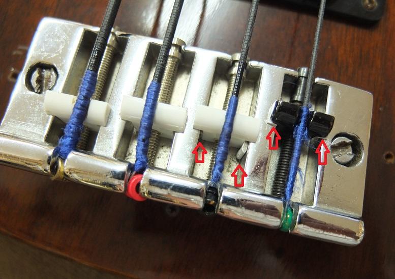 ブリッジ。1弦のサドル、オクターブビスは交換されています。また1,2弦は弦の振動でサドルの共振が目立ったので簡易的に厚紙をはさんで共振防止してあります(赤矢印)。